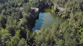 caminhadas : Aerial view from above of a green-tinged lake in a mountain canyon with coniferous forest, tourist camp and bathing people