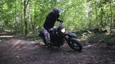 rodas : Steadicam filmed a motorcyclist in protective gear and boots performing a drift around its axis on a motorcycle off-road modification in a clearing in a dense summer forest