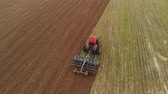 rodas : Aerial view of a powerful energy-saturated tractor with a large hook force, performing tillage for sowing winter crops with a disc cultivator in the autumn Stock Footage