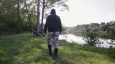 cyclisme : Steadicam saw the slow motion of a rider in motobots and spotted pants approaching a black off-road motorcycle on the banks of a picturesque river near the forest edge Vidéos Libres De Droits