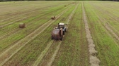 incasso : Aerial view of a tractor producing straw pressing on a harvested agricultural field. From the trailer baler comes ready roll