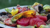 rode paprika : Close-up of appetizing grilled vegetables: peppers, tomatoes, mushrooms, zucchini, stacked in a chrome tray with a pattern on the street. The concept of a picnic in the fresh air