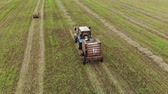 incasso : Aerial view of a tractor with a trailer baler, producing the pressing of straw rolls on a harvested agricultural field. The concept of agribusiness