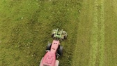 bovini : Aerial view of a farmer on a red tractor with a combined mounted mower with disc rotary knives, producing mowing grass on silage for livestock feed. The concept of agribusiness Filmati Stock