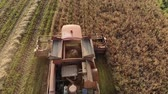 vyrobit : Aerial view vintage combine harvester red producing cleaning of dry crops. Top view of the grain Elevator feeding products into the hopper of the agricultural machine. The concept of agribusiness