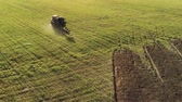 fordulat : Aerial view of agricultural machinery with tillage unit performing paddock plowing farmland waddled in Sunny summer weather. Changing the position of the plow when turning the tractor