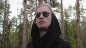 髪型 : Steadicam circular motion of a stylish young European guy in a dense forest. A man in a black hooded cardigan looks around the area with a reflection in his sunglasses. Travel concept