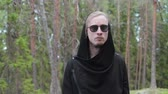 один человек : Portrait of a handsome, young man, blond with a beard in dark glasses and a black cardigan, confidently striding forward against the background of trees, bokeh. Model gait, shooting outdoors, in the woods