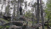 один человек : Stylish European man in a black cardigan and sunglasses descends a rocky cliff in the woods and jumps down. Travel concept