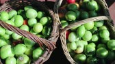 horizontální : Dolly shot a top view close-up of freshly picked green and red tomatoes in wooden brown baskets. Products on the market. The concept of the fall harvest