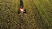 vyrobit : Aerial view. Flying over a combine harvester removing dusty oats in a field of farmland in the autumn evening. The concept of agribusiness