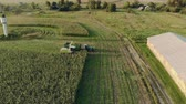 vyrobit : Aerial: harvesting ripe corn with a self-propelled mower in a tractor trailer on a Sunny evening. Drone flight on the background of agricultural buildings. The concept of agribusiness