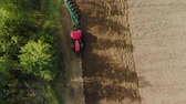 střídat : Aerial view of a farmer in a modern tractor cultivating the soil for sowing with a trailer plow on support wheels with many ploughshares Dostupné videozáznamy