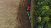 střídat : Aerial view of a farmer in a modern tractor cultivating the soil for sowing with a trailer plow on support wheels with many ploughshares. Drone takes off from the top of the object