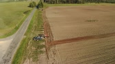 horizontální : Aerial: a farmer on a red tractor with a disc harrow turns around near the highway and cultivates the soil for sowing seeds. The drone follows the object. The concept of agribusiness