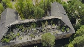 gebroken : Aerial: flying around an old abandoned concrete house in a Park. The buildings slate roof and rafters have collapsed, and trees are sprouting through the structure. The concept of chaos