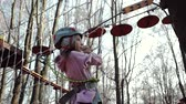 udatnost : Steadicam shot of a happy little girl in a rope Park against the background of a forest. A child in a helmet and protective equipment passes the track and holds onto the net. Active rest on the nature Dostupné videozáznamy