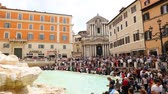 história : May 12, 2018, Rome, Italy. Crowd of tourists at Trevi Fountain. Tourists in Rome at Trevi Fountain. Church of Saints Vincent and Anastasius in Piazza di Trevi in Rome.