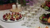 começando : In poured a glass of champagne, the bubbles go up, a table decorated with flowers. in the background are snacks at the buffet, the average plan Stock Footage