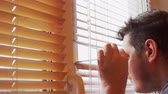 sbirciare : curious man looks out the window through the blinds