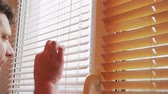 gluren : curious man looks out the window through the blinds