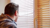 serio : curious man looks out the window through the blinds