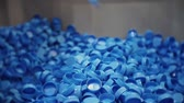 produtos químicos : blue plastic corks fall into a large box. Stock Footage