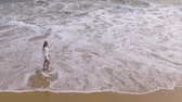 oregon coast : A young girl in white dress is walking on beach with ocean waves