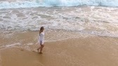 oregon coast : Slow motion aerial shot A young girl in a short white dress is walking on sandy beach in hikkaduwa