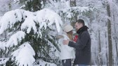 conta : Snow falling on couple in love in winter forest