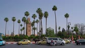 Cars and busses passing the big mosque in Marrakech