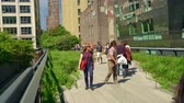 locals and tourist enjoying the nice weather on the Highline walkway in downtown Manhatten