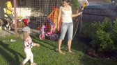 sprey : Woman watering the lawn Stok Video