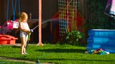 hosepipe : Little girl watering lawn