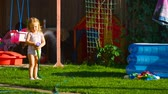 famílias : Little girl watering lawn