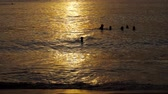 золотой : Beautiful sunset with silhouettes of people enjoy the ocean.