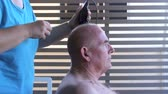 kazınmış : Profile view of a middle aged elderly man getting a close hair cut with hair clippers. Stok Video
