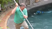kamie�� : Middle aged man cleans the corner his swimming pool with long brush.