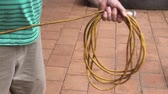 extension : Man rolls up electrical cable into a tidy roll after use. Stock Footage