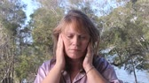 agitated : Middle aged woman outside with headache rubs her temples and head.