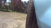 ímpeto : Low angle POV shot of front car wheel driving on a dirt road and stopping.