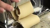 flatten : Reverse angle close up putting dough into pasta maker then rolling dough through the machine. Stock Footage