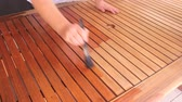 do it yourself : Person painting a wooden table with varnish with a paintbrush by hand.