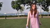 delighted : Asian chinese woman in slow motion walking on grass lawn
