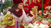 jemioła : Pretty young woman buying floral compositions at Christmas market