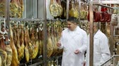 serrano : Technologist with butcher checking drying wurst and jamon at factory