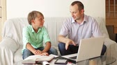 working parents : Father helping teenage son to do homework at home