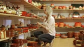 crock : cheerful female customer picking crockery in ceramics workshop
