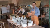 crock : two cheerful artisans having ceramics in hands and standing in workshop