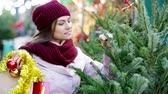 vinte anos : Smiling woman staying at market among Christmas trees Stock Footage